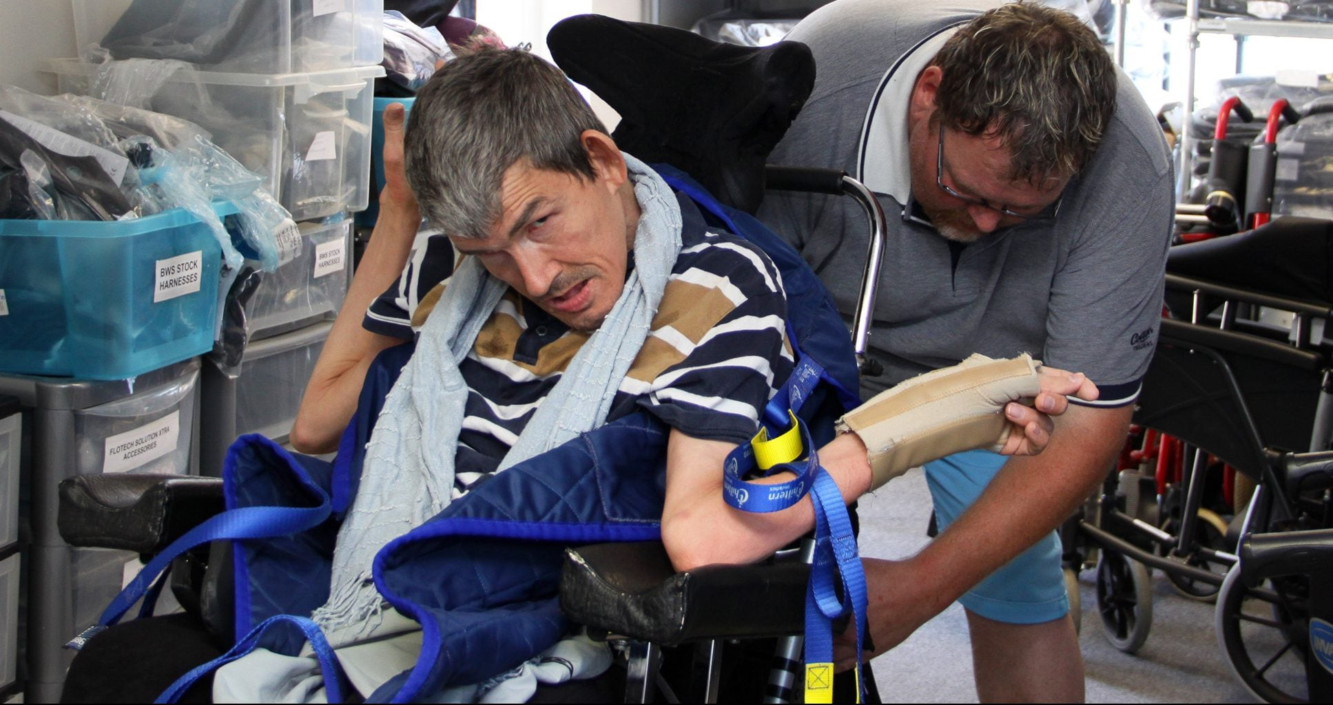 A disabled man being strapped into his wheelchair by a carer.