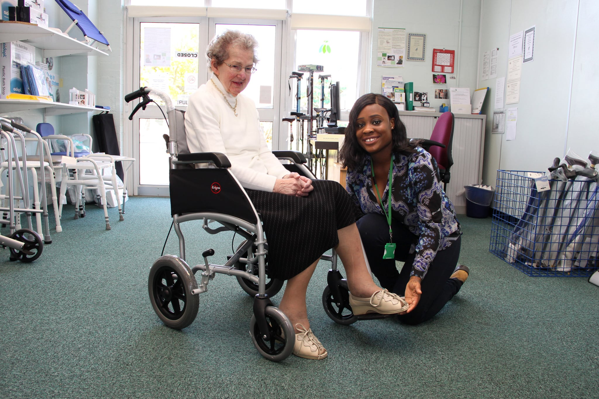 An old woman in a wheelchair with a carer.